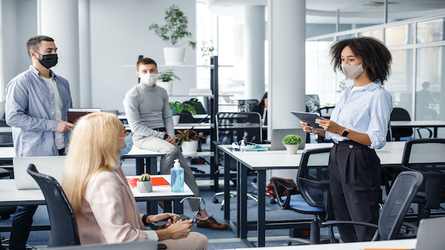 Corporate meeting and group work in company. African american woman manager in protective mask holding tablet, talking to workers keeping social distance